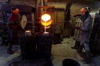Marcel and Daniel pour molten bronze into the ceramic encasing for the James Martin sculpture